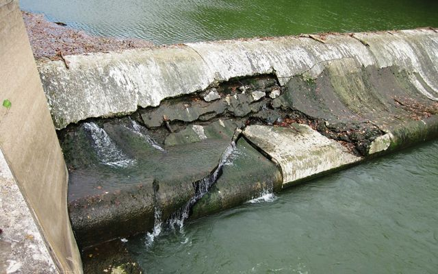Concrete dam with cracks and areas that are crumbling.