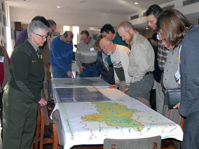 People gather around a map.