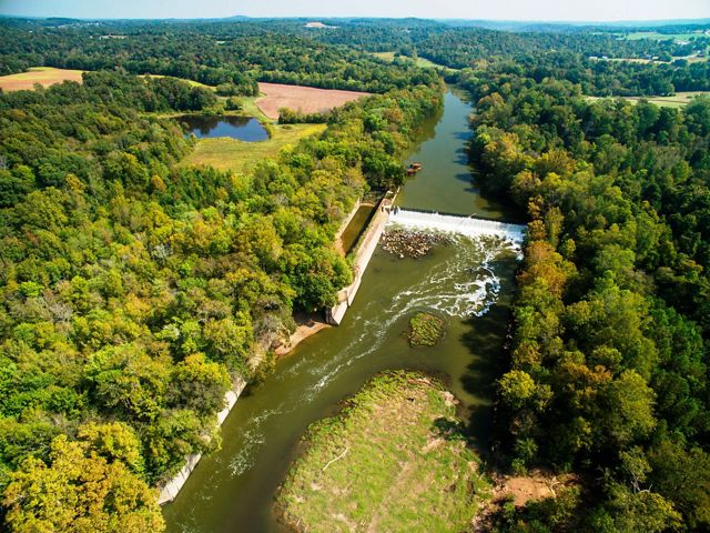 A river flows past farms and forests.