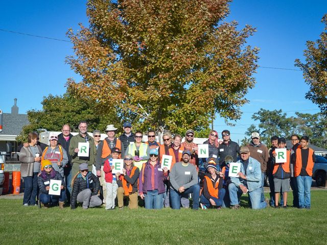"A large group of volunteers poses for a photo holding letters that spell out the word ""greener."""