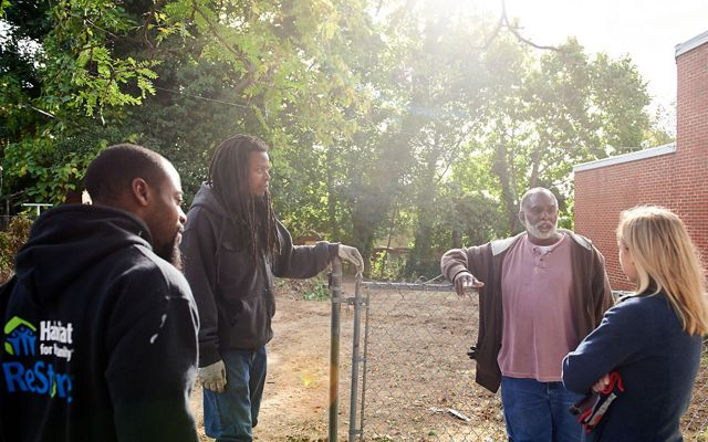 Three men and a woman having a conversation stand together next to a vacant lot that is being cleared for tree planting.