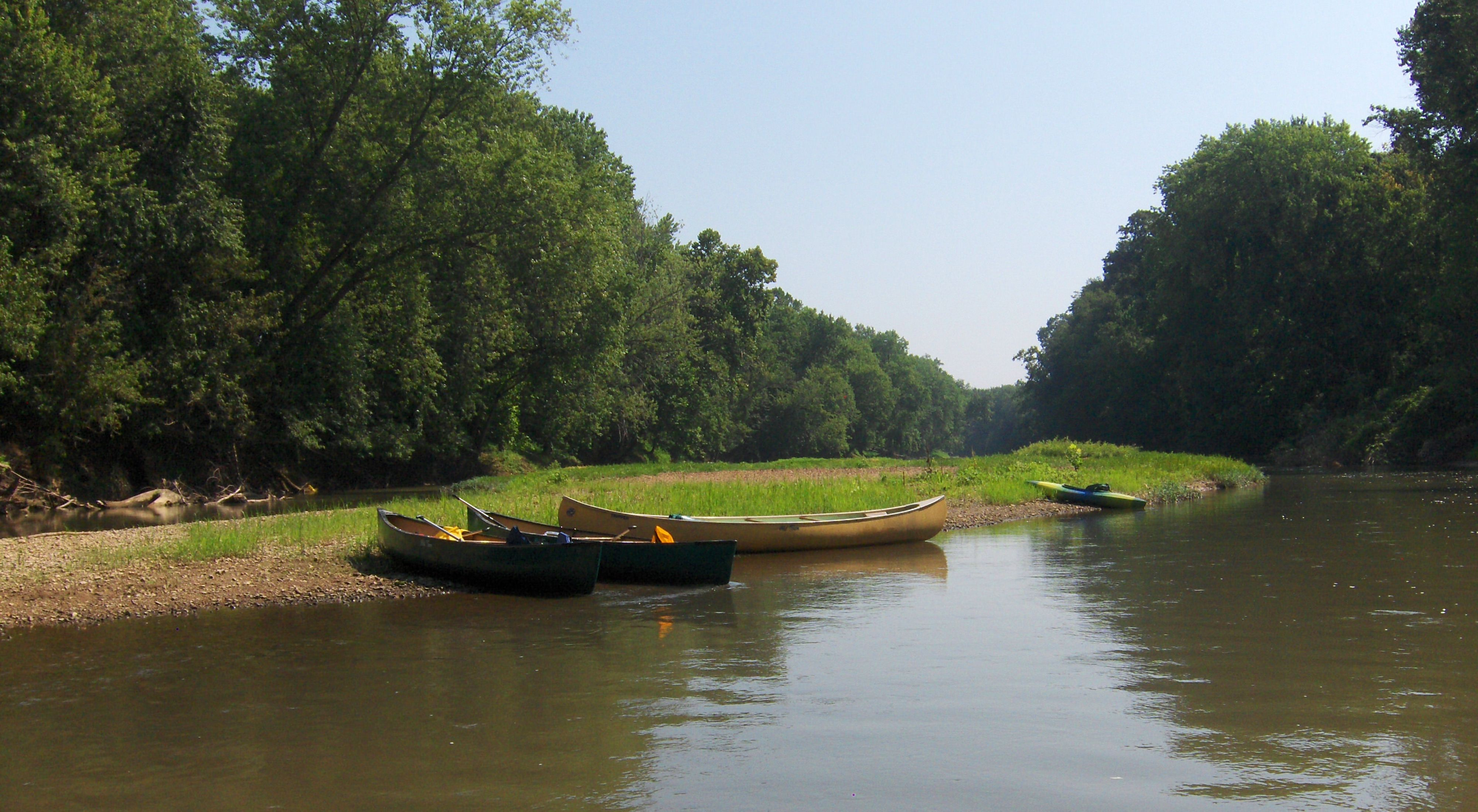 Three canoes and a kayak sit on the side of a river bank.