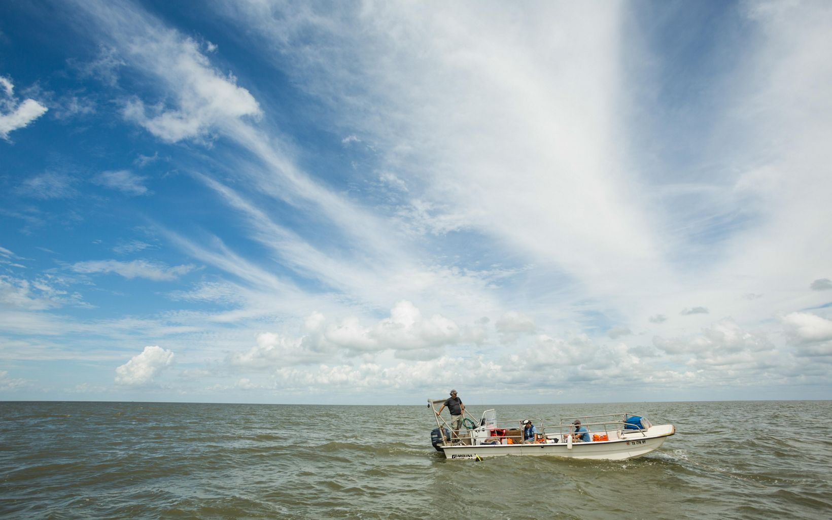 A small motor boat on the water under a blue sky with scattered clouds.