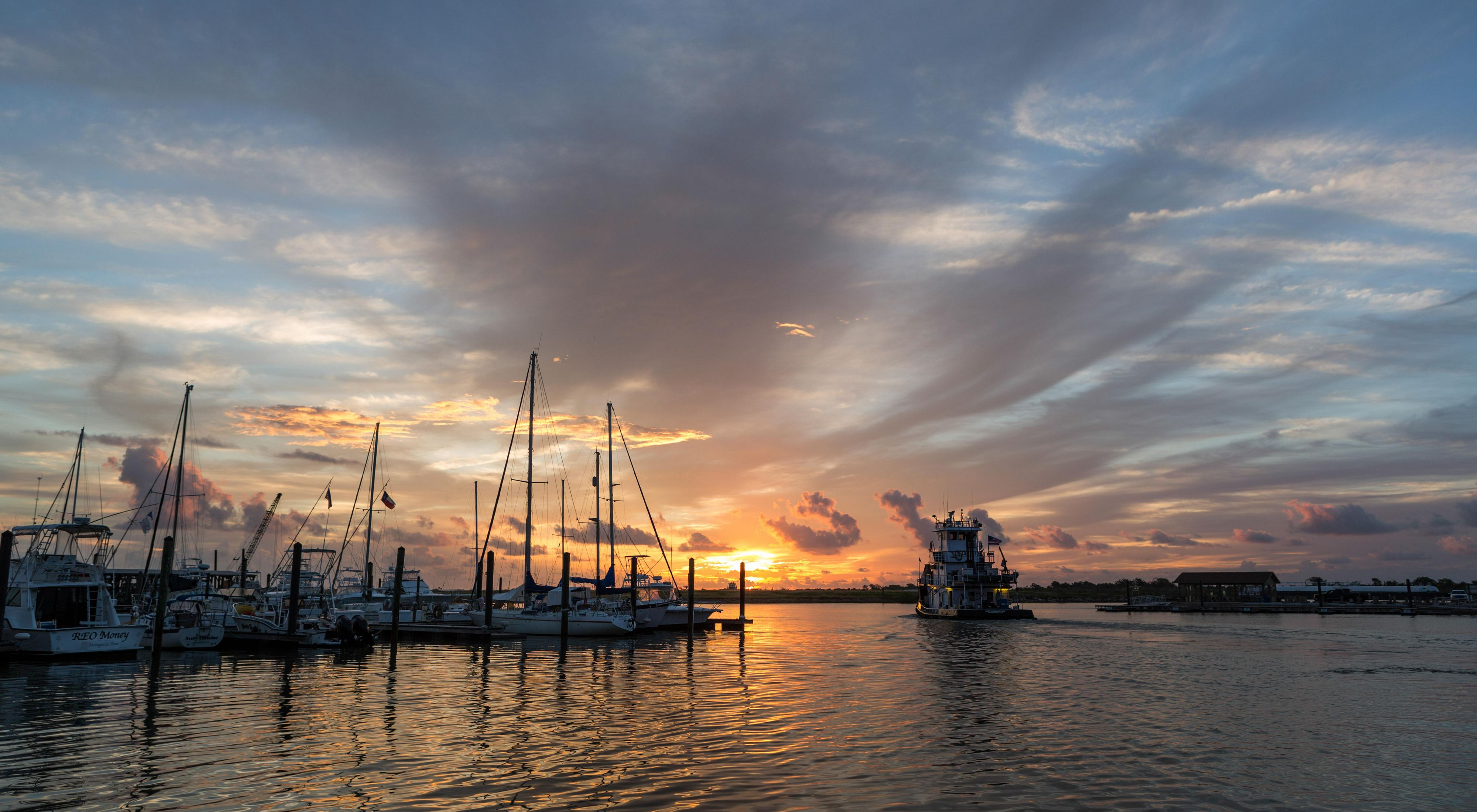 A marina full of sailboats with an orange and pink sunset behind it in a cloud-streaked sky.