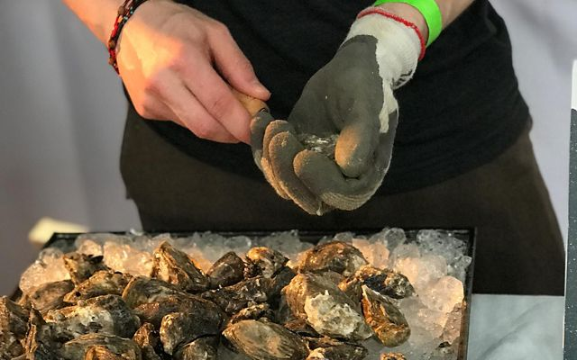 A person wearing a glove shucking oysters.