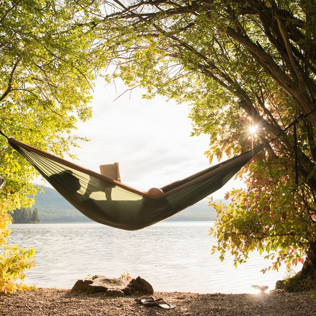 A person reading in a hammock by a lake.
