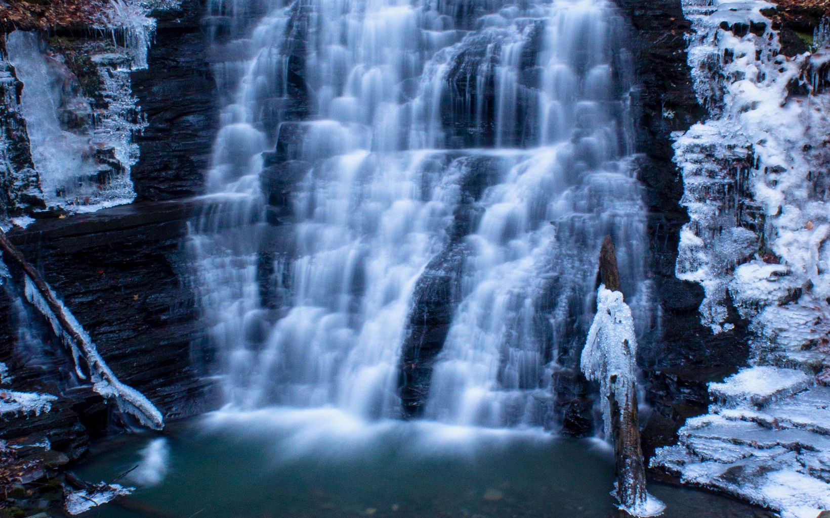Waterfall with frozen ice on surrounding rocks.