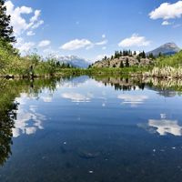 Mountain landscape reflected in clear blue lake.