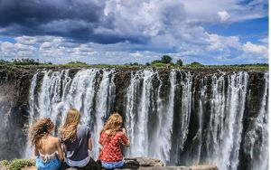 People sitting in front of a waterfall