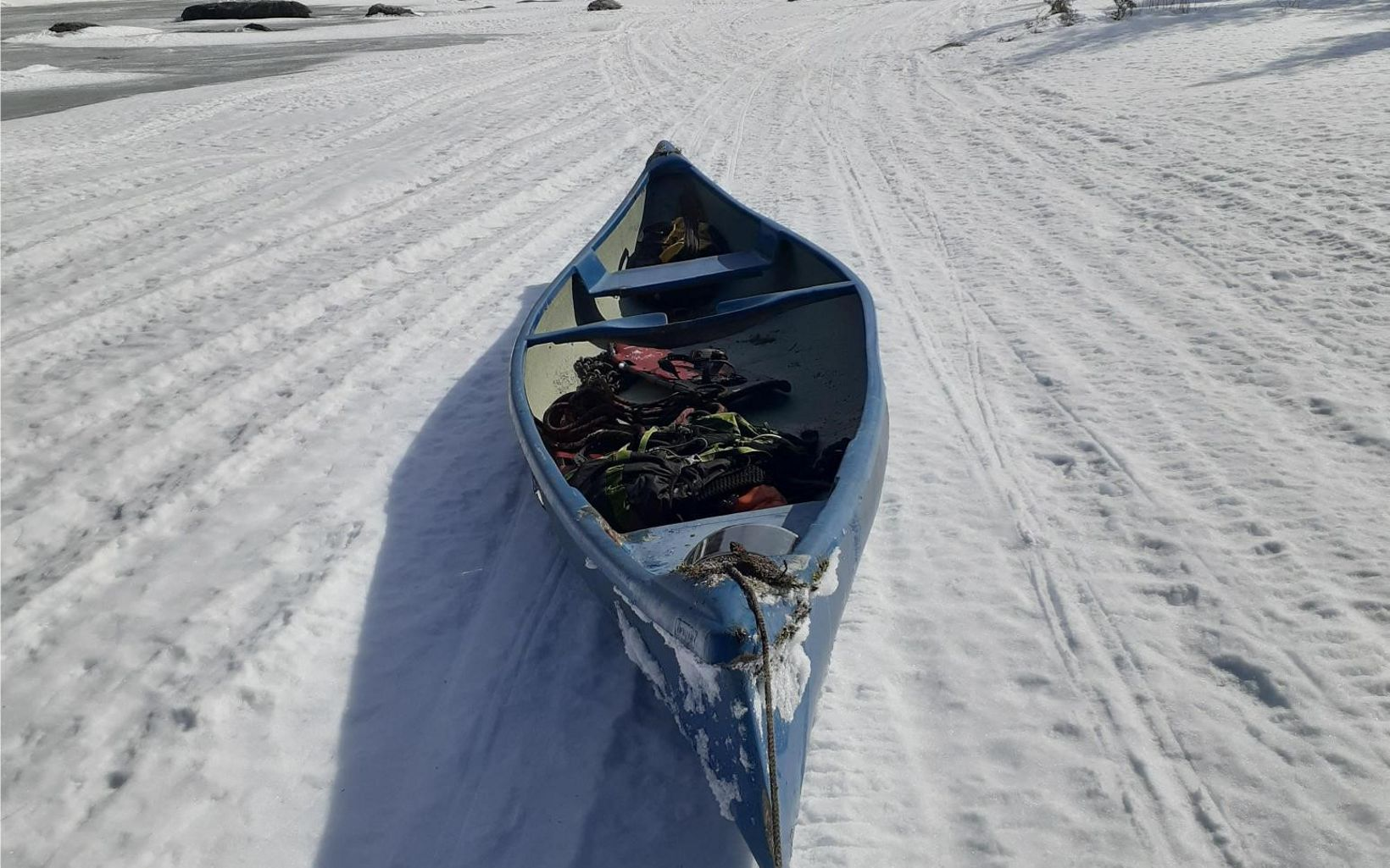 View from snowmobile of a canoe towing behind in the snow.