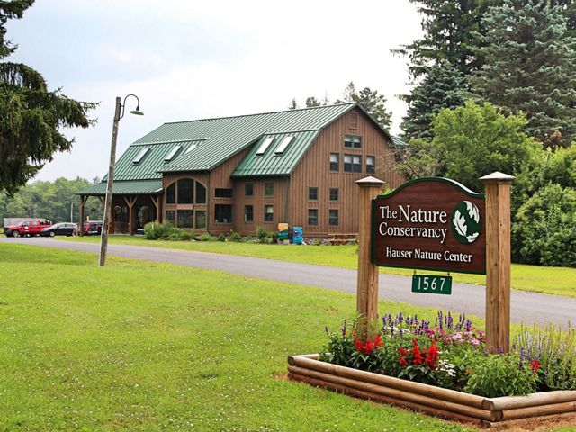 A nature center sign identifies a  brown building.
