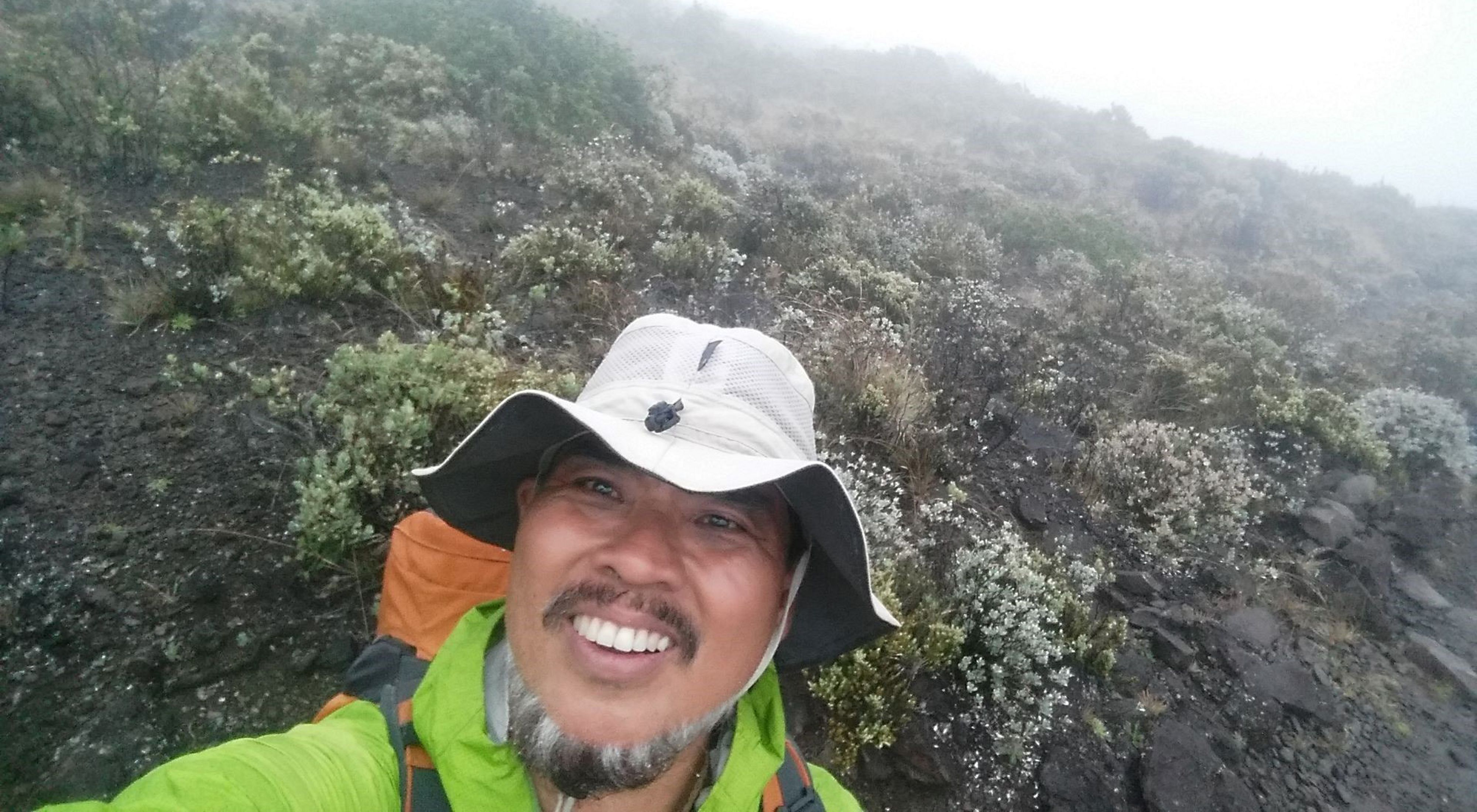 Sam Gon smiles in a selfie in front of a foggy, rocky mountainside with small shrubs and mosses growing amongst the rocks.