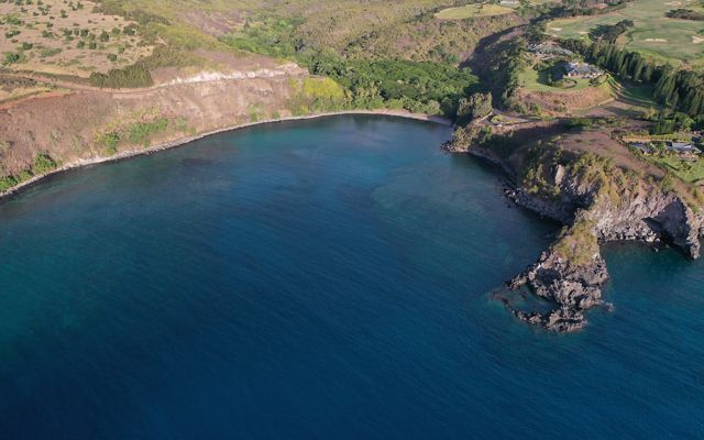 Aerial view of a deep blue bay with a rocky shoreline.
