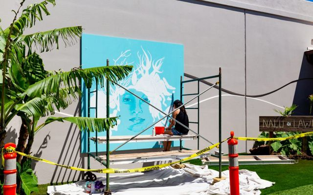 An artist sits on scaffolding painting a mural of a woman with marine organisms for hair and a bright turquoise background.