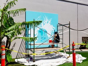 Artist Jana Ireigo sits on scaffolding painting a mural of a woman with marine creatures in her hair on a bright turquoise background.