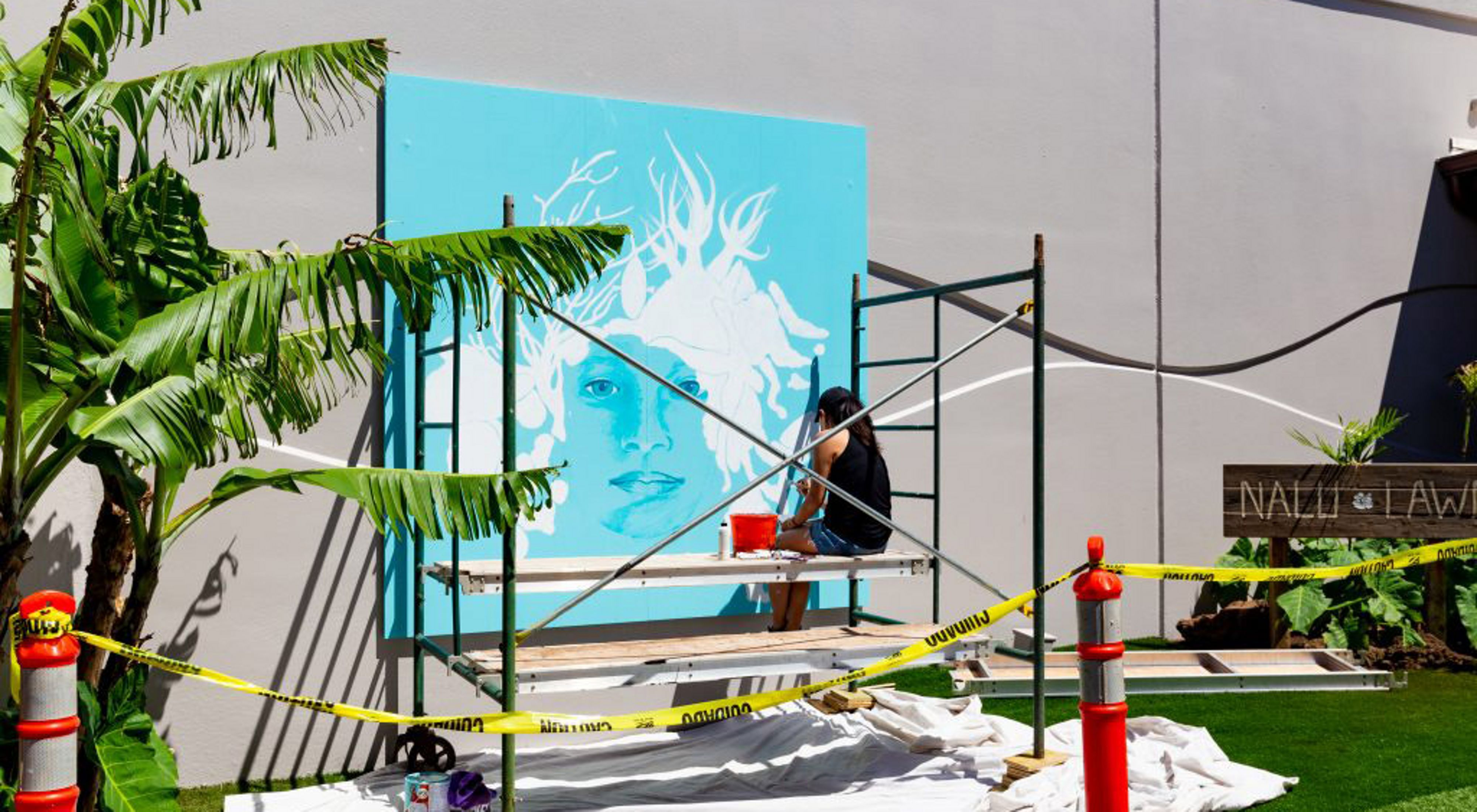 An artist sits on scaffolding, painting a large mural depicting a woman with marine creatures for hair on a bright turquoise background.