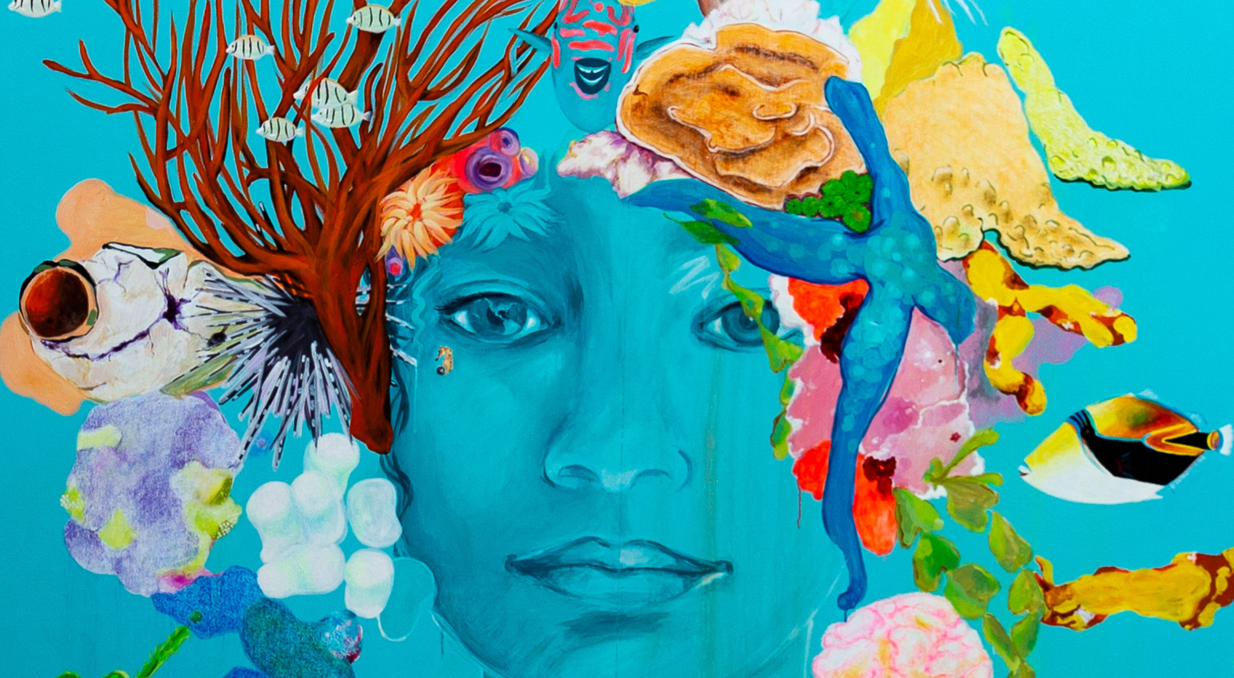A bright turquoise mural of a woman's face with sea creatures as hair.