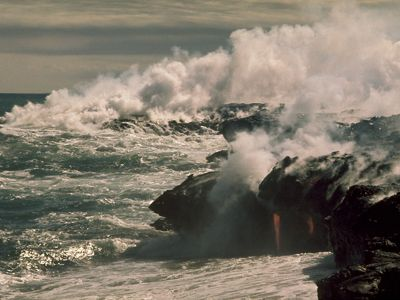 Molten lava flows into the sea creating clouds of steam at Hawai'i Volcanoes National Park.