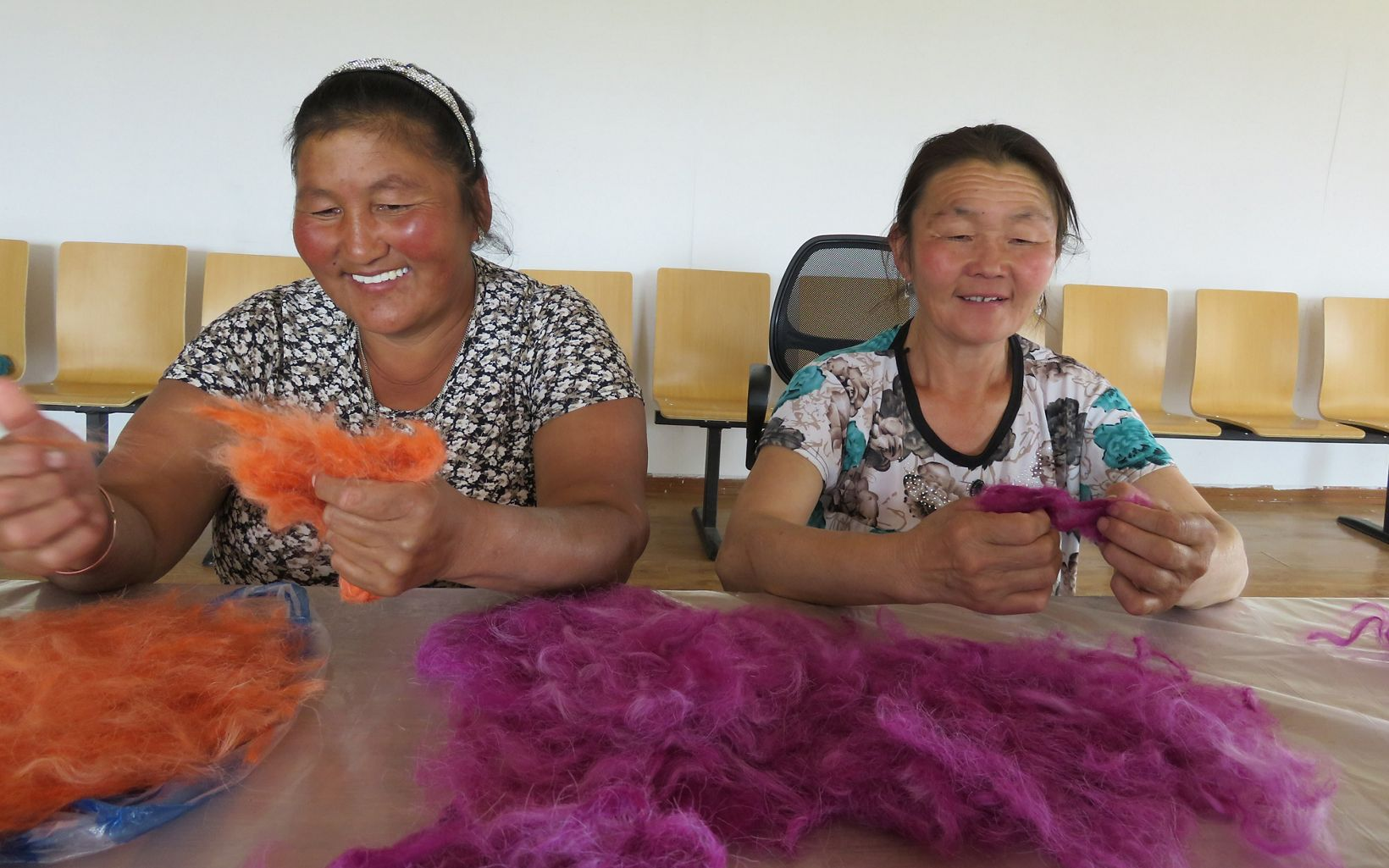 Two herder women smile while working on separating colored wool.