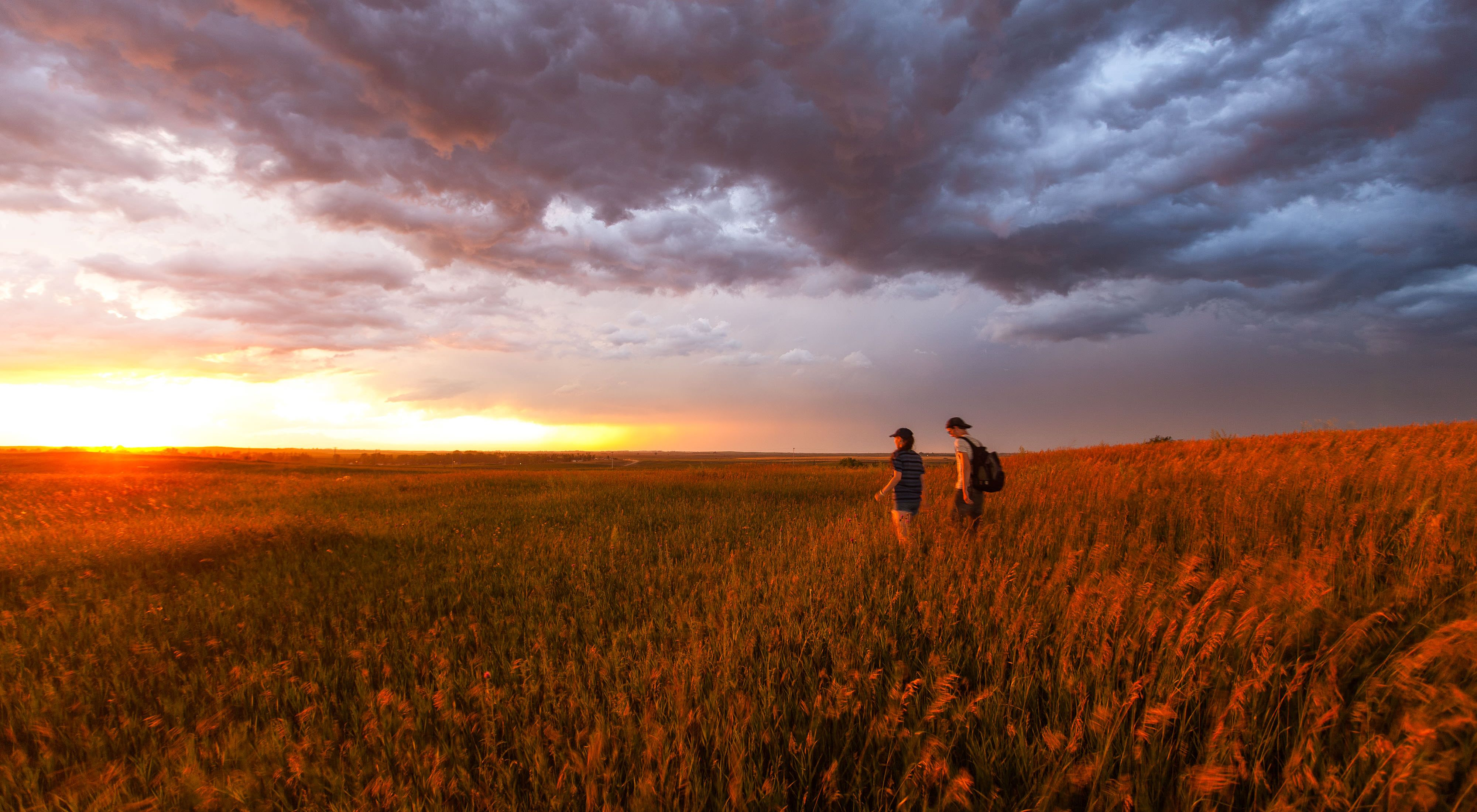 Two hikers walking in a prairie toward the setting sun