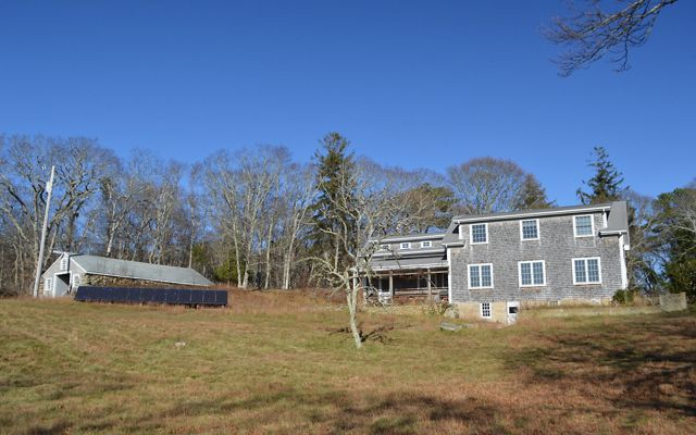 A gray shingled house sits on a grassy hill with a solar panel array to the left of it and trees and blue sky in the background.