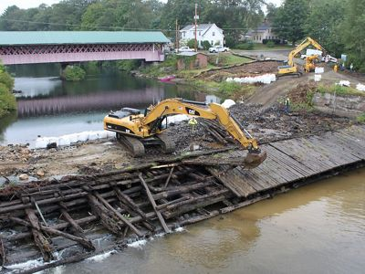 Heavy machinery remove wooden timbers from an old dam in a river.
