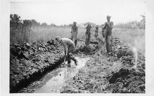 Black and white photo from 1935. Five men holding shovels stand at the end of a wide ditch filled ankle deep with water. One man is in the ditch bent over digging.