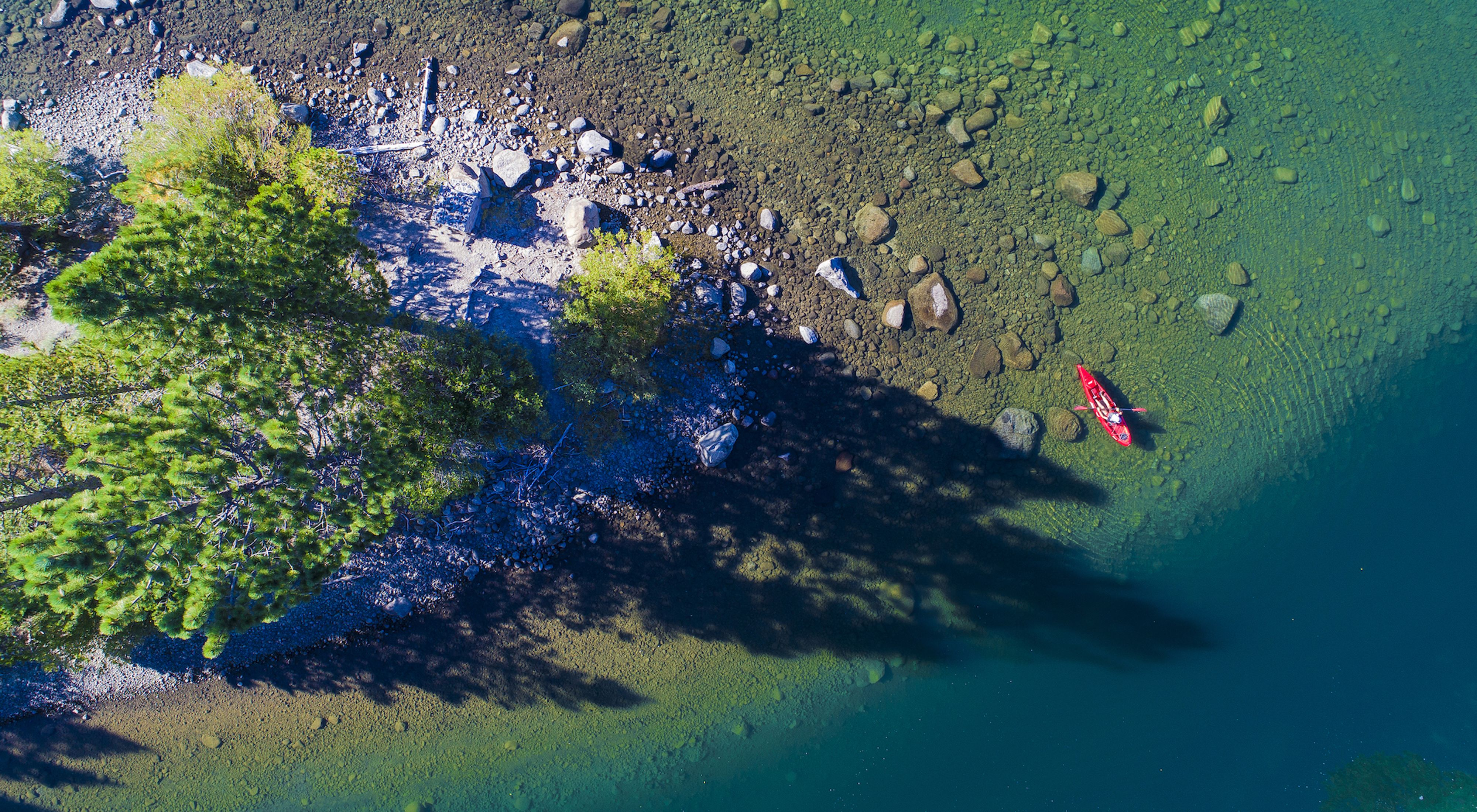 Looking down on the clear blue-green water of Independence Lake with a single red kayak floating near the shoreline.