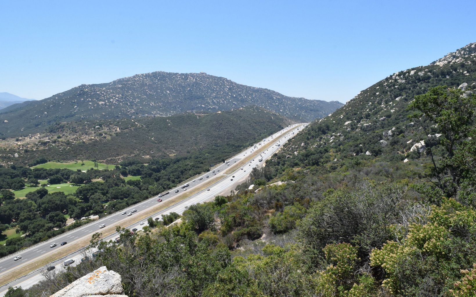 an eight lane highway cuts through two large mountains in Southern California