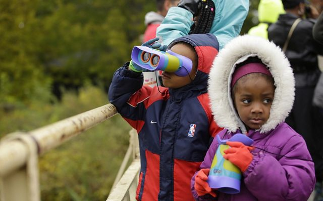 2 young kids at a park in Chicago peer through binoculars specifically made for children.
