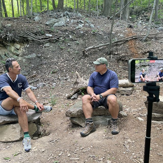 Two men sit together in a forest. They are each sitting on stacked boulders. The ground rises steeply behind them. In the foreground, an iPhone mounted on a tripod records their conversation.