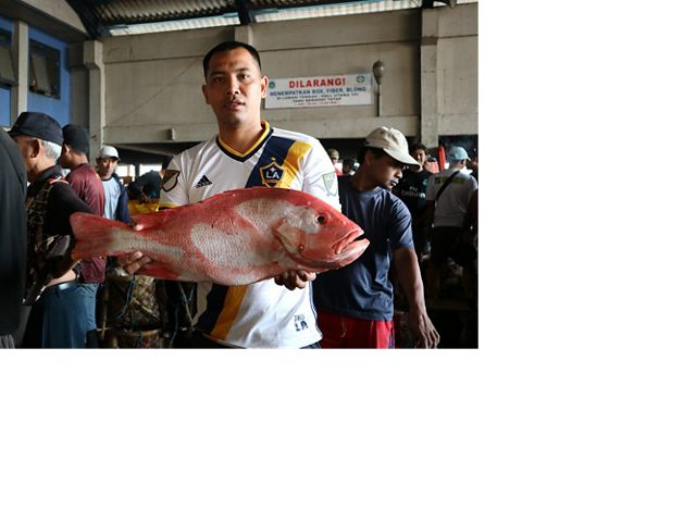 A man holds a large red fish in a busy market.