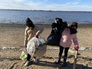 Two young girls bundled up in winter coats stand on a sandy beach holding up garbage bags filled with trash collected during a volunteer event.