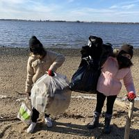 Two girls standing on a beach holding large plastic bags filled with trash. They are both bundled up against the cold and wearing face masks. The water behind them is calm.