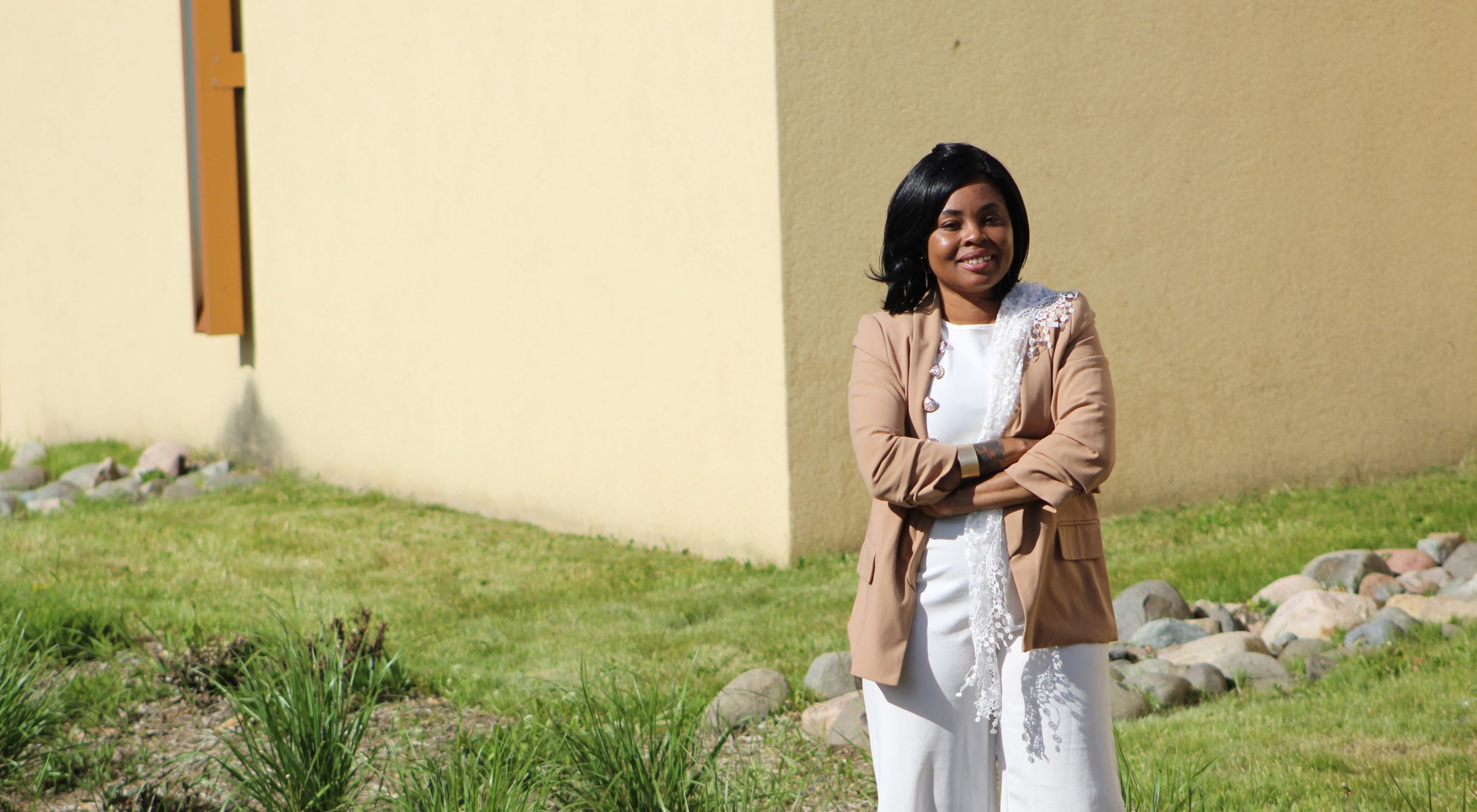 A smiling Kenya McKnight Ahad stands in front of a tan building with grass and rocks forming a bioswale.