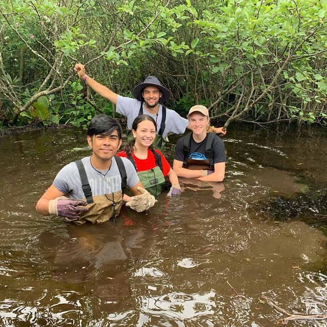 Four people stand in chest deep brown water.