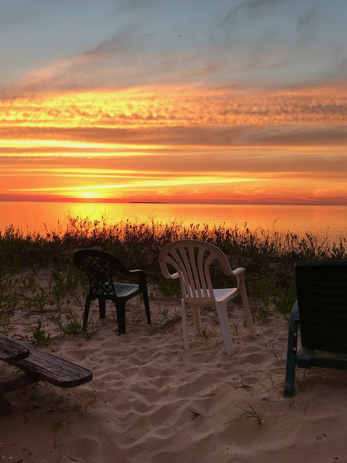 Chairs on the coast of Lake Michigan during a sunset