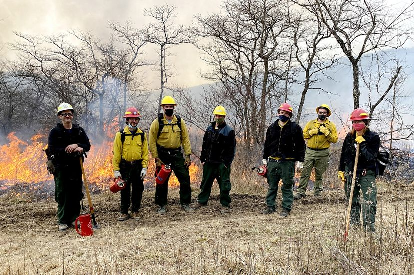 Seven people pose together in a line during a controlled burn. They are wearing yellow fire gear and some hold red drip torch canisters. Fire burns through the tall grass behind them.