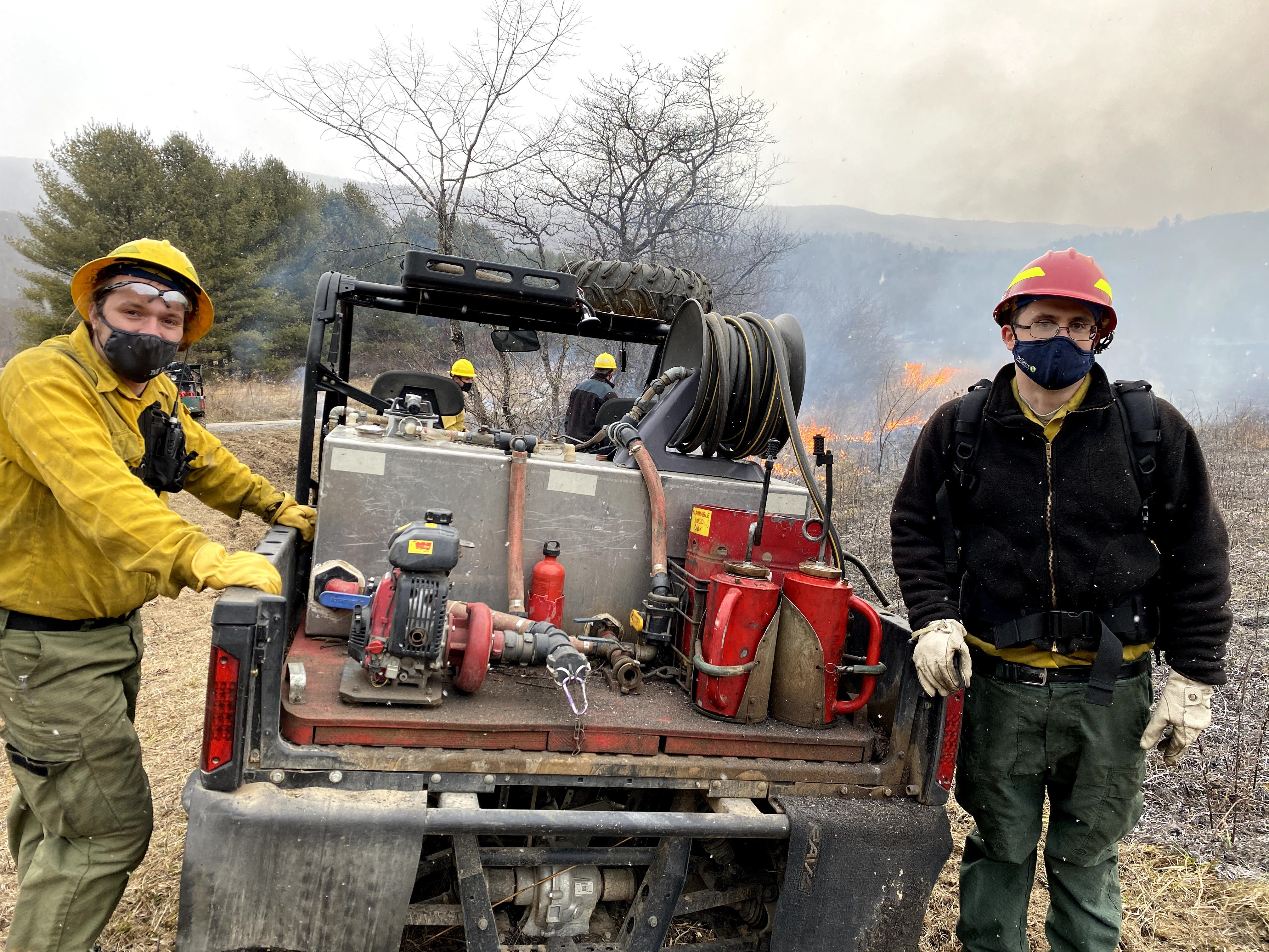 Two men wearing fire gear stand on either side of a small fire engine. Behind them two men monitor a fire during a controlled burn. The air is filled with flecks of either snow or ash.