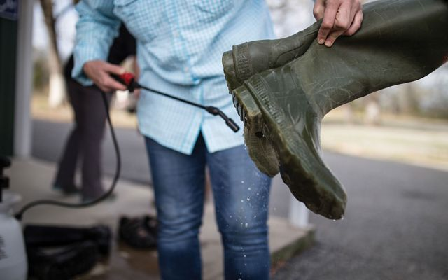 TNC staff cleaning boots with bleach spray after use at Pontotoc Ridge Preserve.