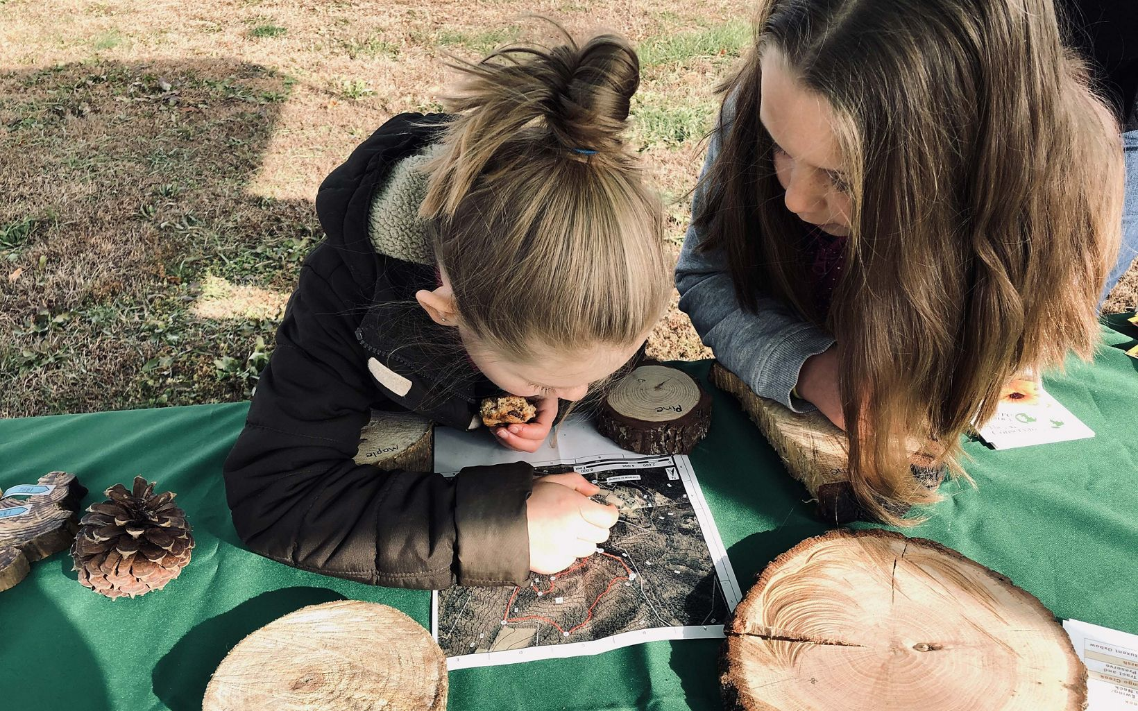 Sisters Annelie and Sadie enjoy cookies and examine a map at TNC's public viewing station during the Sideling Hill Creek Controlled burn, November 21, 2019.