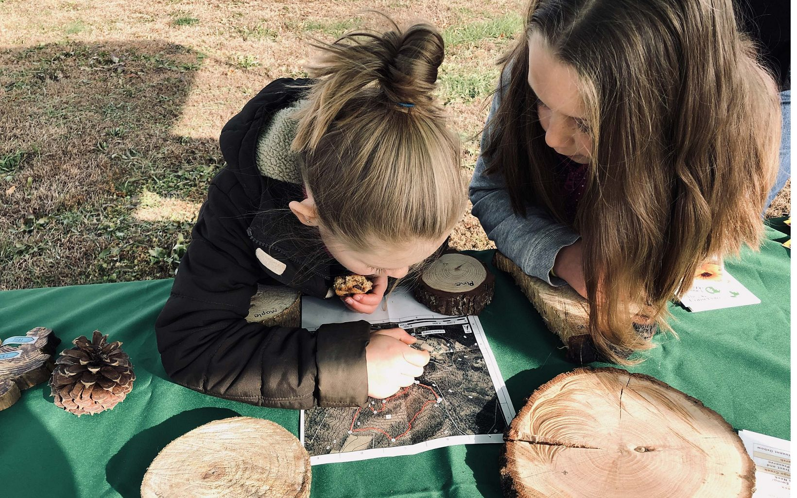 Two girls leans their elbows on a table bending over a map to closely examine it.