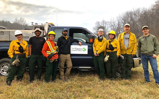 Members of the Maryland fire team pose in front of a truck following a controlled burn at Sideling Hill Creek Preserve.
