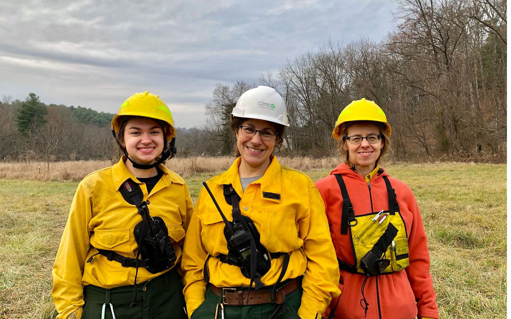 Three women wearing yellow fire gear stand together.