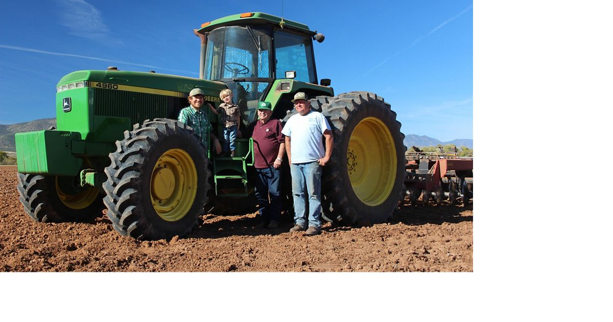 four people stand in front of a tractor