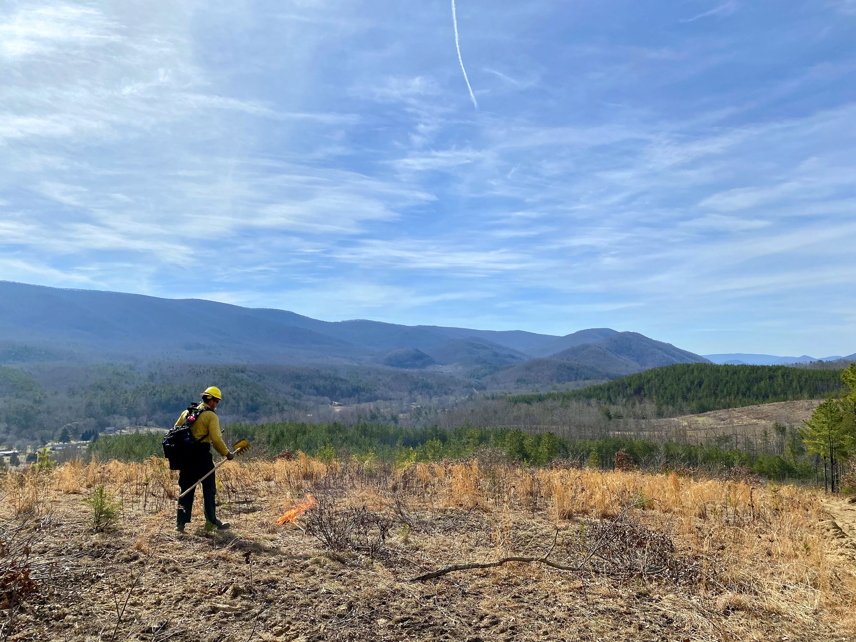 A man wearing yellow fire gear stands in an open field next to a small fire that is burning itself out. Tall mountain ridges line the horizon in the background under a bright blue sky.
