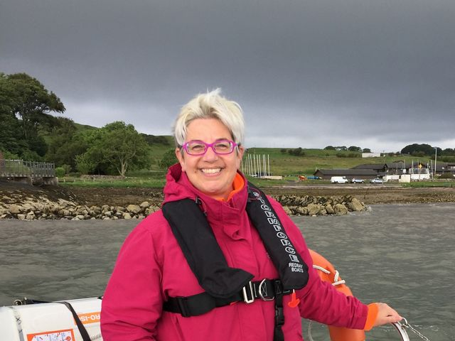 Candid photo of Digital Content Manager Whitney Hall. A smiling woman wearing a pink jacket and black personal flotation device stands at the back of a small open boat.