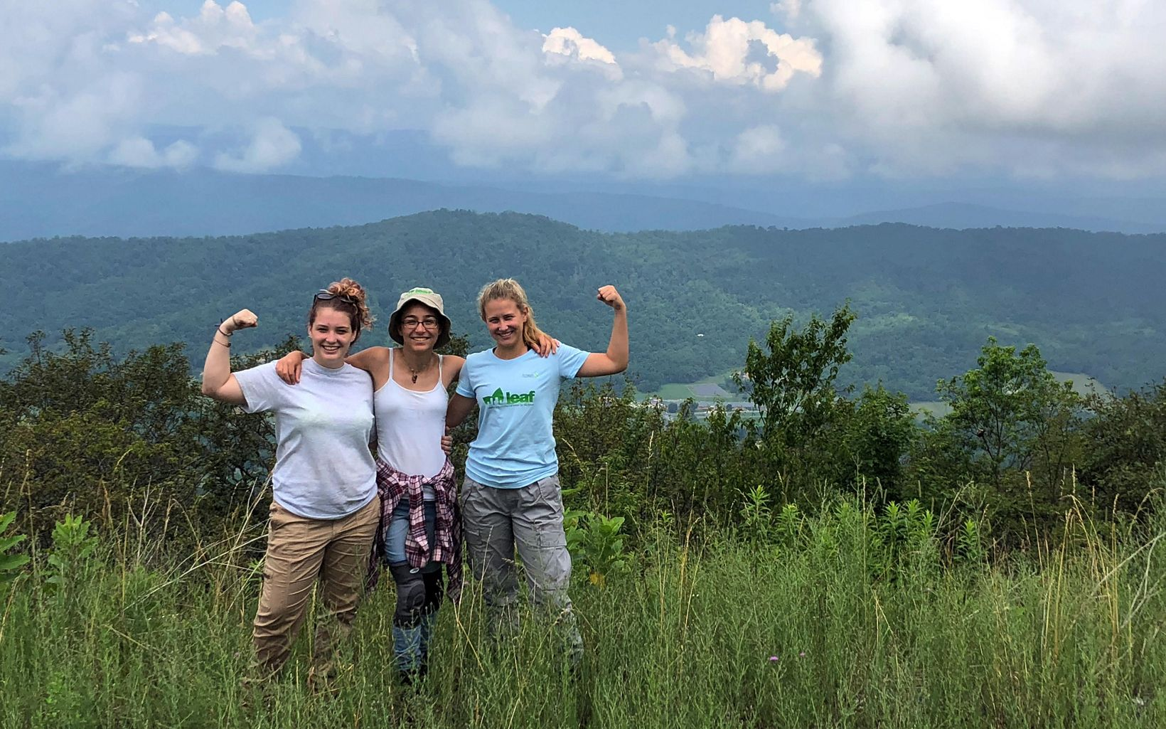 Three girls stand together arm in arm in tall grass. A valley drops away below them ending in a line of mountain ridges.