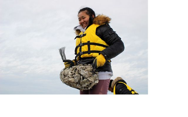 A woman holds a mesh back full of loose oyster shells.