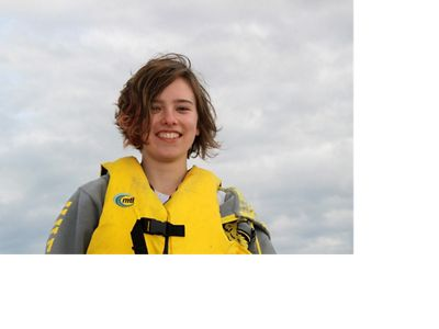 A smiling woman wearing a yellow life jacket.